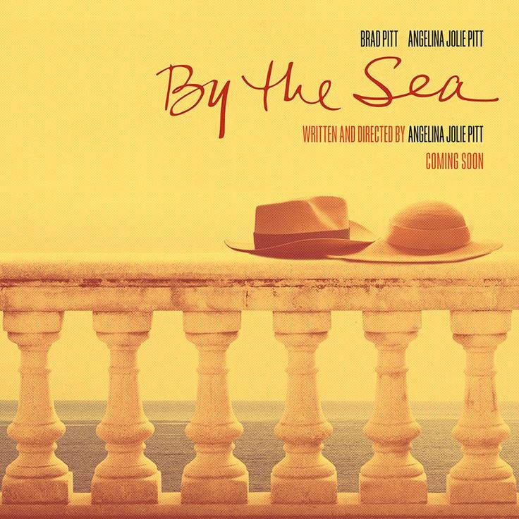 Cartaz do filme by de sea de Angelina Jolie com dois chapeus de palha, um masculino e um feminino, sobre uma mureta de frente para o oceano