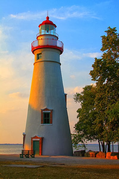 White lighthouse with red trim, shore of Lake Erie, large tree