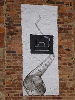 Wand, mit Nähmaschine und Maßband bemalt