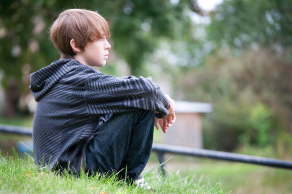 Young boy sitting on a hill