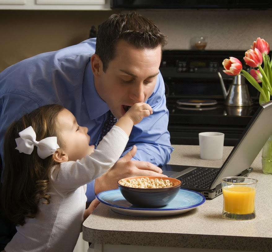 Young daughter feeding cereal to her father