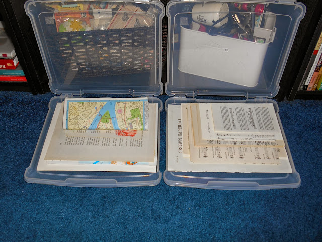 two clear storage containers filled with book paper, maps, and sheet music