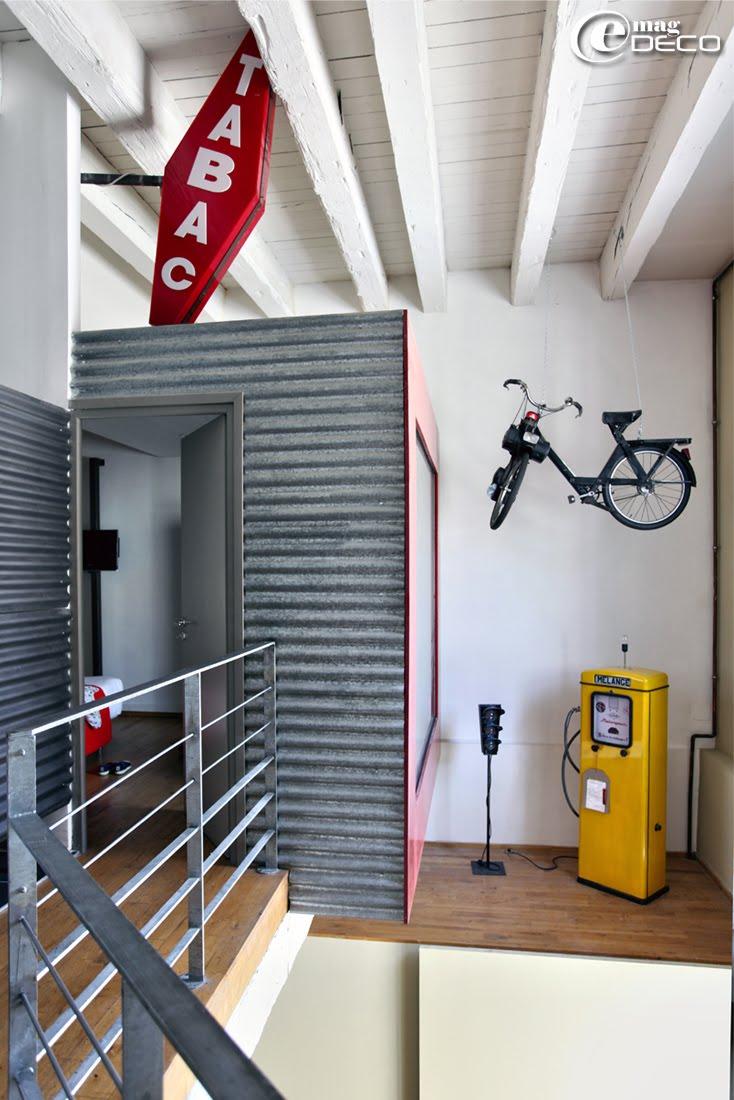 Décor urbain d'un loft à louer à Marseille, Solex ancien suspendu au plafond, pompe à essence vintage