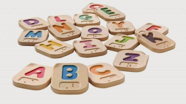 Descrição: Retângulos na cor creme com cantos arredondados. Eles tem aproximadamente o tamanho da palma da mão. Letras coloridas do alfabelo da lingua portuguesa e em Braille estão estampados nas peças.  Fim da descrição. Link: http://www.reab.me/crianca-cega-tambem-brinca-conheca-brinquedos-para-os-pequenos-com-deficiencia-visual/