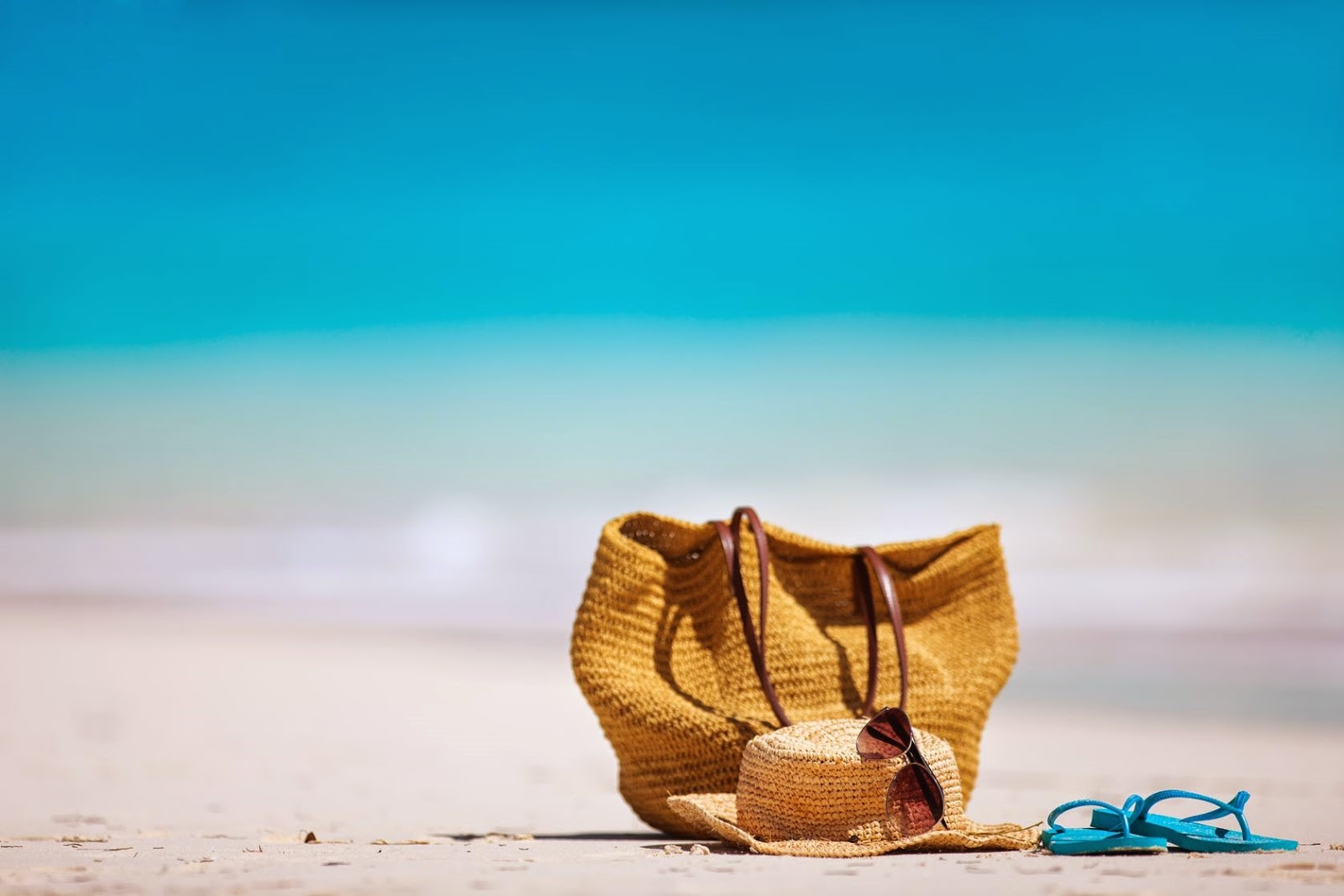 A discarded purse, hat, sandals, and sunglasses on a beautiful beach.