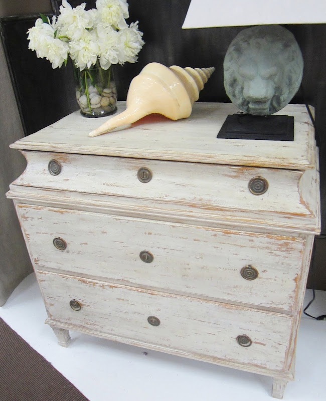 Swedish 3 Drawer Chest by Tara Shaw Maison with a large sea shell, flower arragement and lion portrait