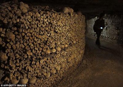 GAMBAR tidak bertarikh menunjukkan seorang pengkaji  terowong itu berjalan di barisan tulang dan tengkorak manusia.