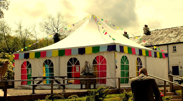 marque with colourful bunting and dramatic sky line