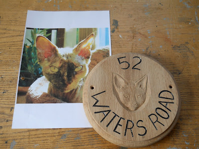 carved portrait of a cat in wood
