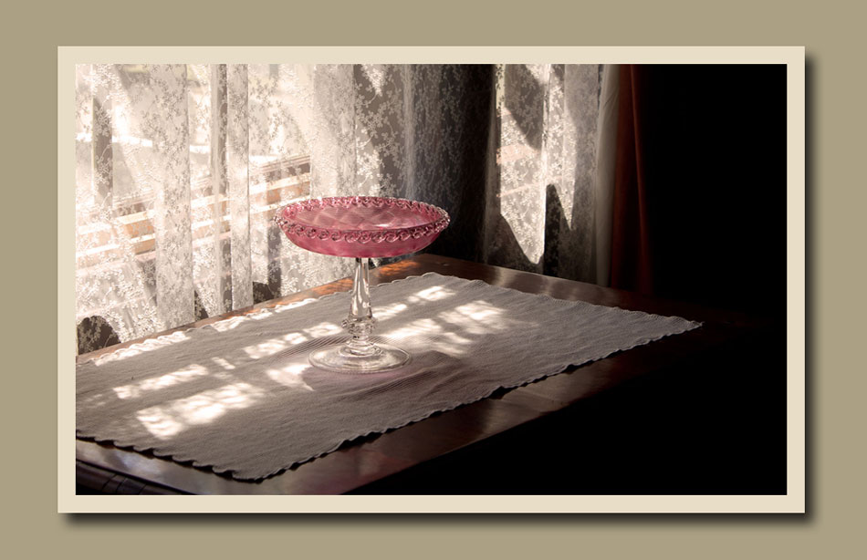 A cranberry glass compote in the light filtering through lace curtains in Burwick House at Black Creek Pioneer Village.  Holly Cawfield Photography