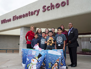 Image of Wilson Elementary students and teachers alongside Rio Salado College staff at front entrance of school.  Donations are in gift bags in front.