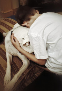 Diesel the dog and his boy Gage embracing as they prepare for a final goodbye.