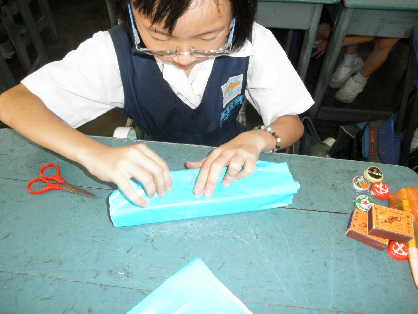 Murid meratakan gam dan membalut kotak menggunakan kertas warna