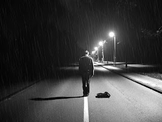 Homem sozinho na rua escura e chuvosa com luzes ao fundo e mochila no chão.