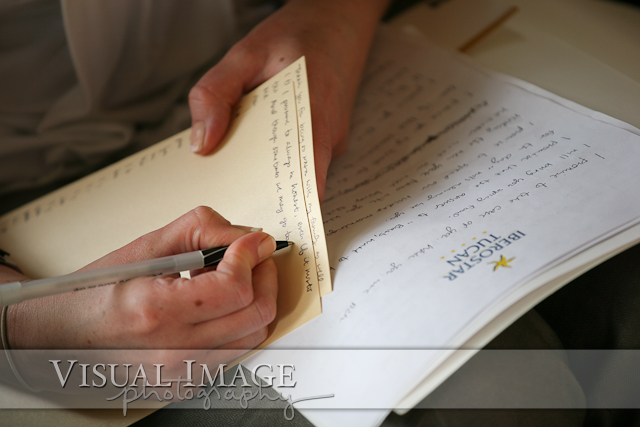 Bride writing love note to husband before wedding