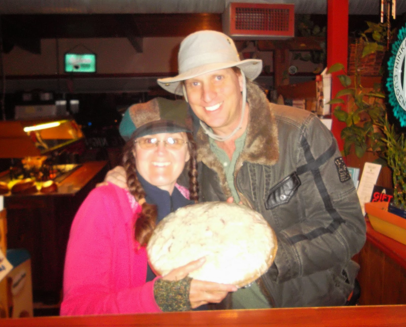 Cynthia M. Parkhill and Jonathan Donihue holding plastic-wrapped, uncooked pizza at restaurant counter.