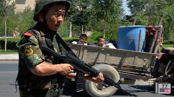 Một cảnh sát Trung Quốc có vũ trang đóng tại một trạm kiểm soát trên con đường dẫn tới thị trấn Lukqun