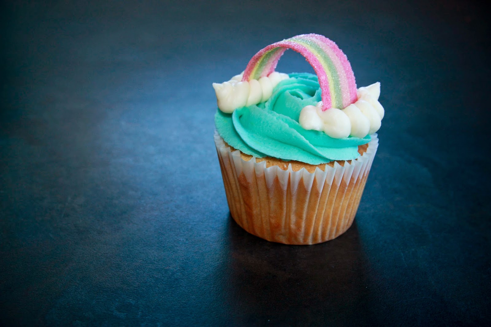 Lemon and passion fruit cupcakes topped with a piped blue butter cream rose swirl, piped clouds and a rainbow belt sweet