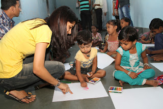 A volunteer at Aarambh helps children draw and paint.
