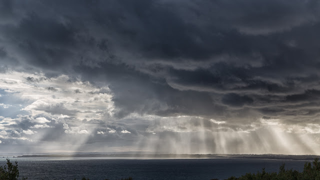 sun rays behind dark cloud ocean
