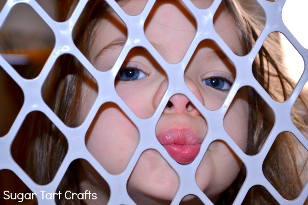 toddler girl with her face pressed against a baby gate
