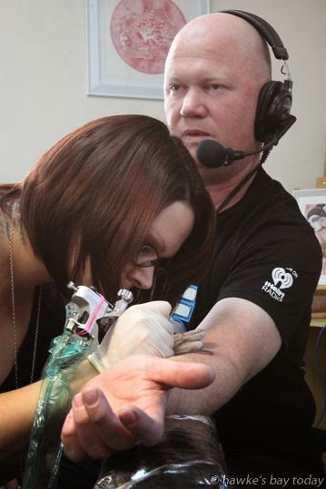 Sarah van Der Kley and Martin Good, co-hosts on the radio breakfast show on The Hits, were tattooed by Emma Kerr, tattoo artist at Spacifik Ink Tattoo Studio, Napier, in support of a fundraiser for Melinda de Vos, Napier, to get tattoos to cover up her burn scars. photograph