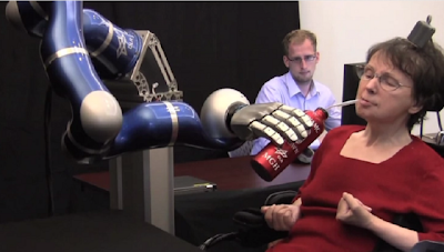 cathy getting a sip of coffee from a bottle held by a robotic arm.