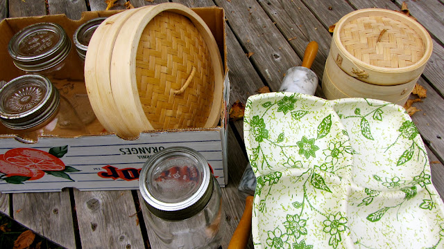 thrift store finds including mason jars, bamboo steamer, rolling pin and tray laid out on a wooden deck