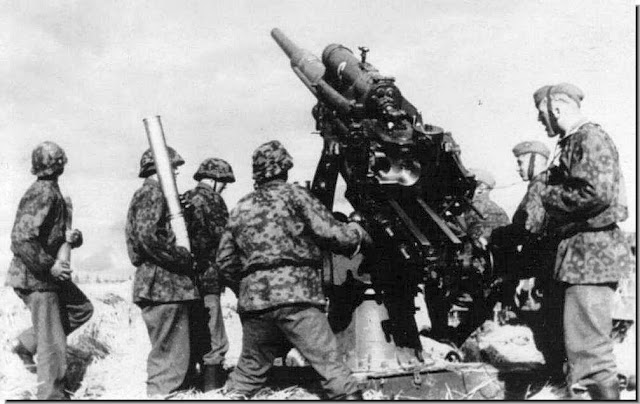 Waffen SS soldiers fire the formidable German 88mm gun. It acted both as a tank-buster and as anti-aircraft gun.