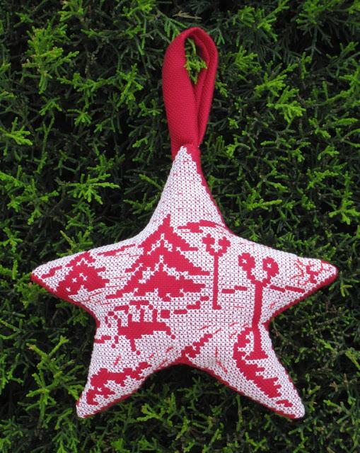 Adorno con forma de estrella bordado a punto de cruz blanco sobre rojo