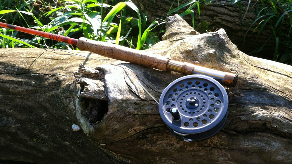 A Fenwick fiberglass fly rod resting on a log beside a trout stream.
