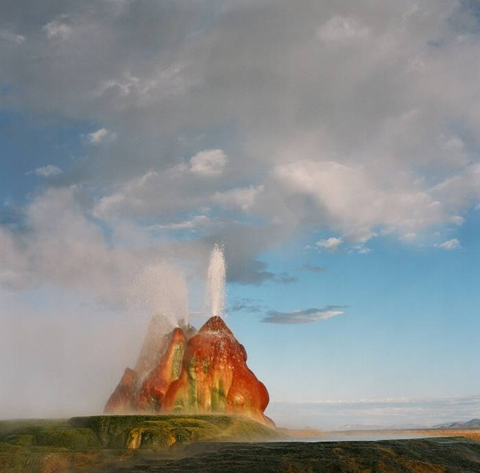 Fly Geyser is a little-known tourist attraction, even to Nevada residents. It is located near the edge of Fly Reservoir and is only about 5 feet (1.5 m) high, (12 feet (3.7 m) counting the mound on which it sits). The Geyser is not an entirely natural phenomenon, and was accidentally created in 1916 during well drilling. The well functioned normally for several decades, but in the 1960s geothermally heated water found a weak spot in the wall and began escaping to the surface. Dissolved minerals started rising and accumulating, creating the mount on which the geyser sits, which continues growing. Today water is constantly spewing, reaching 5 feet (1.5 m) in the air. The geyser contains several terraces discharging water into 30 to 40 pools over an area of 30 hectares (74 acres). The geyser is made up of a series of different minerals, which gives it its magnificent coloration.