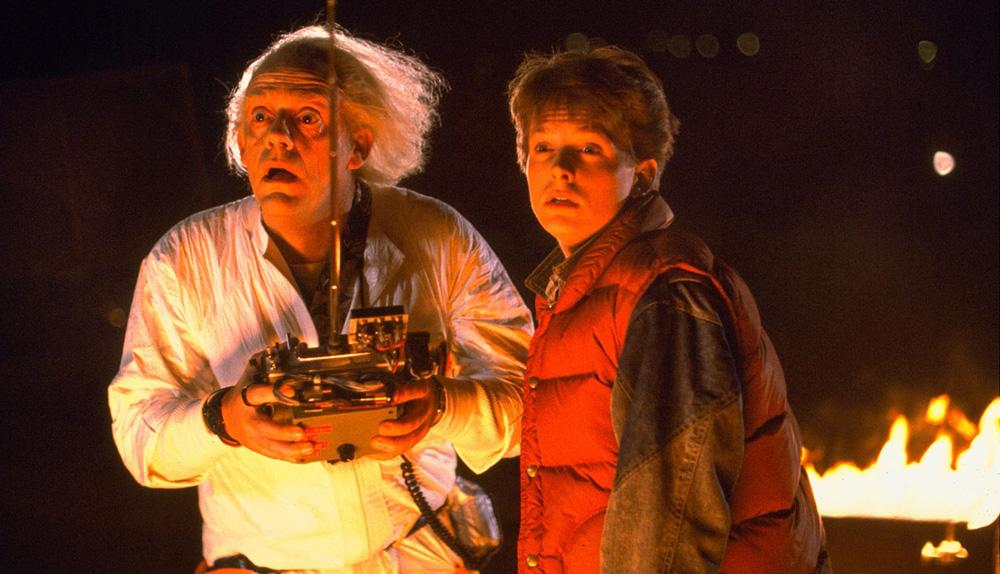 cena do filme de volta para o futuro na qual o doutor Emmett Brown, Christopher Lloyd, usa um controle remoto para dirigir o delorean ao lado de Marty McFly, Michael J. Fox
