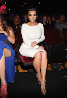 Kim Kardashian shows off her legs sitting down in a red chair