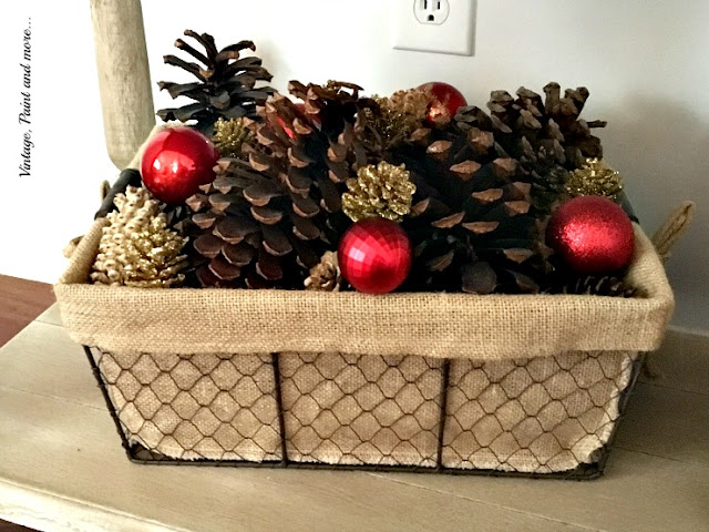 industrial wire basked with burlap liner filled with pinecones and ornaments