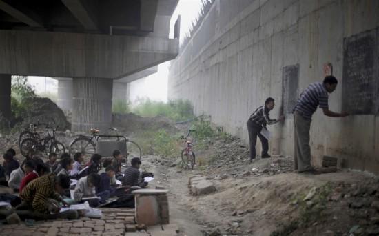 Educación donde sea – niños indios desfavorecidos asisten a la escuela al aire libre bajo un puente