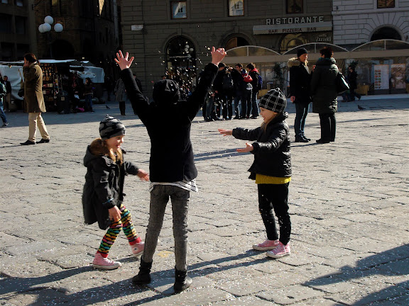 little girls throwing confetti in piazza republica