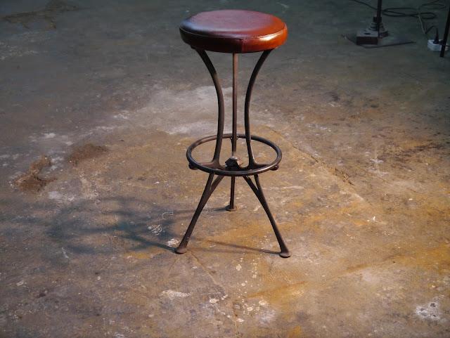 Taburete de hierro fundido con asiento de piel ( cuero) con un tratamiento de envejecimiento satinado