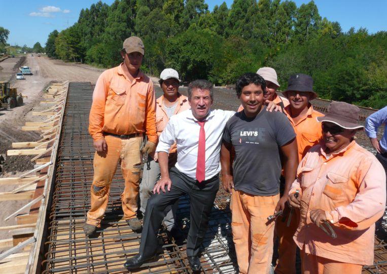 El gobernador provincial junto a los obreros que construyen el puente en el ingreso a Las Moscas