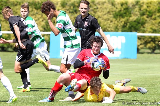 Red: Charlie Morris, guest player, goalie, Birkenhead (the black team) saves a goal attempt from a corner and bumps into Elliott Munford (yellow) the goalie from the other end (Western Springs) who came down to help, in the final minutes of the game - Birkenhead beat Western Springs 1-0 in the final of the Napier City Rovers under-19 football tournament at Park Island, Napier. photograph