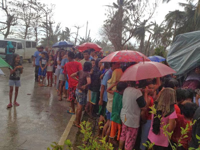 Yolanda victims lining up for relief goods in the rain