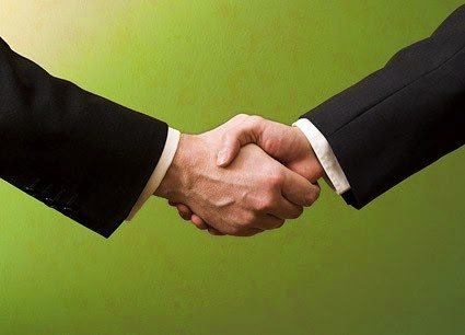 a picture of two men shaking hands dressed professionally
