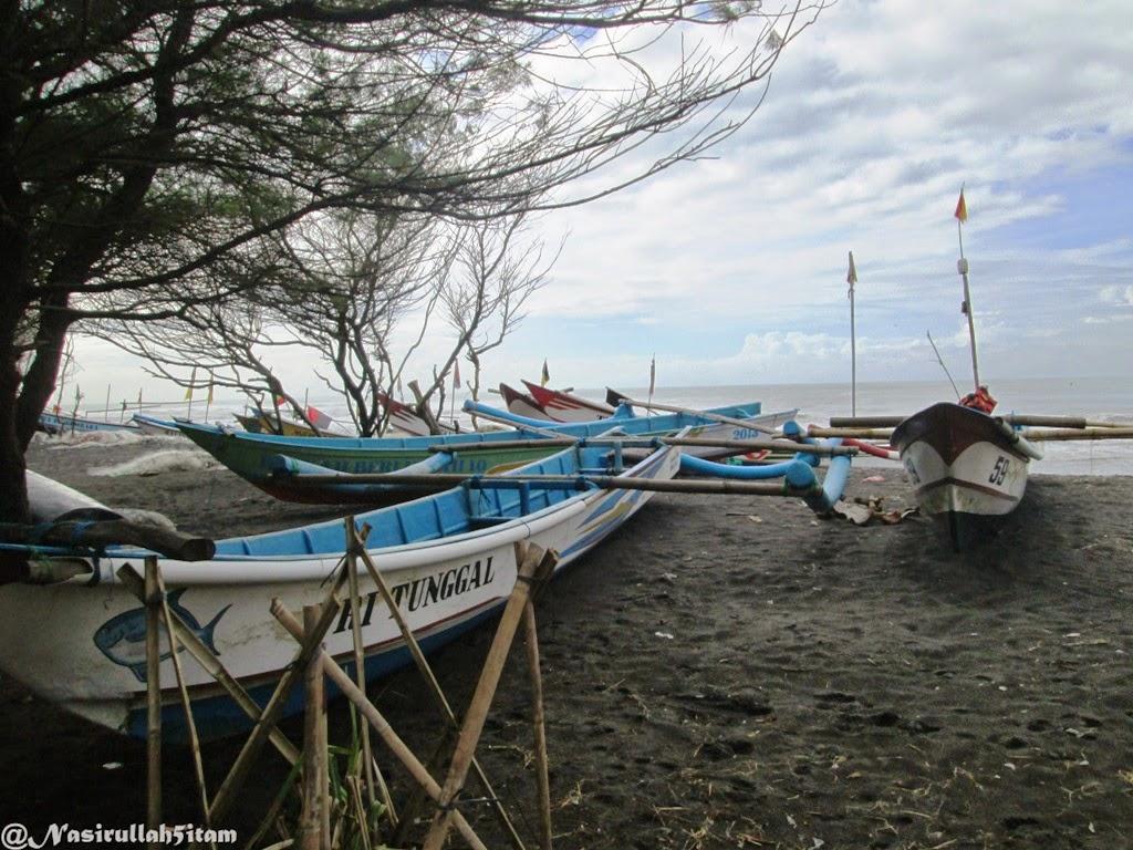 Kapal nelayan tergalang di tepian pantai