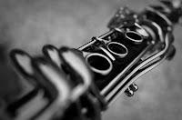 Pormenor da zona intermédia de um clarinete, evidenciando os furos e desfocando as chaves para cá e para lá deles