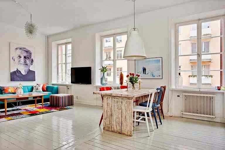 Skandynawskie wnętrze i piękny drewniany stół z drewnianych desek oraz kolorowe krzesła