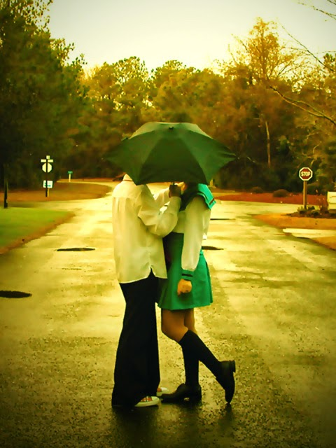 Couple Kissing Under Umbrella At The Road