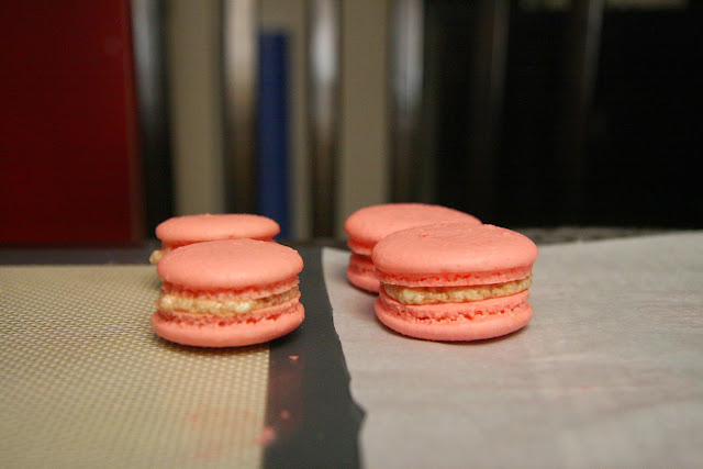 Visual comparison between macarons baked on silicon mats versus parchment paper.