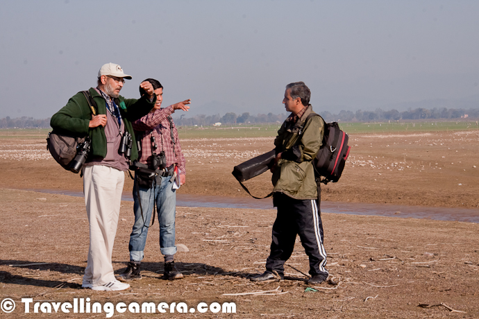 After regular follow-ups for last one year, finally I attended official Bird Counting activities at Pong Wetland during Jan'2012. Initially it was more of a Photography trip for me, but finally it proved as a very knowledgeable & inspirational trip. Apart from learning lot of stuff about birds, I got an opportunity to meet various birders and Wildlife Professionals. Let's know more about these folks and how they think about nature & these colorful birds...A photograph of Sarbjeet Kaur, who is an active member of Chandigarh Birder Club and travel a lot for birding. She was carrying this huge Tripod and Canon Camera with 100-400mm lens all the time. On each day, we walked around 10 kilometers around shorelines of Pong Dam Lake in zig-zag manner. I was amazed to see her enthusiasm that the way she was taking care of her gadgets apart from 100% contributions in counting birds. And believe me, it's not at all a easy thing to walk with such heavy gadgets..Here is whole team of Chandigarh Bird Club !!!  ( Sarbjeet Kaur, Rima Dhillon and Navjit ). After talking to these folks, I realized that they keep traveling or at least keep planning birding activities around Chandigarh. After Bird Counting at Pong Dam Lake, they had to go to Nangal for some other Birding event. After this, there was something planned on weekend for World Bird Day !!! Above all, I think there is something happening on 12th Feb as well. If you are truly interested in knowing what all is happening at Chandigarh Bird Club, join  them on Facebook at https://www.facebook.com/groups/166751020061454/Here comes Mr. Rahul Jain with his Gadgets for watching birds at Pong Dam Lake ! He is one of the member of Delhi Bird Club... As per him, he is not as active in birding as other members of Delhi Birding Club are. During this trip, he also visited Dharmshala & Mcleodganj. Apart from Birding he is keen interest in History and Indian Heritage. He was the one who had come to Pong with full plan of visiting Monolithic Temples of Masroor and most of us also joined himHere are four birders who were in our troop of two teams, which used to start from one point. Everyday we started from one point and moved in opposite directions. During these counting sessions, one section covered by a team is done by another team, to avoid counting errors. Although this counting can't be 100% correct, but professionals known what plus or minus needs to be done as per geographical location with different characteristics in terms of location, weather and other things. I am sure you must have noticed snow covered Dhauladhar Mountain Ranges in background of this PhotographMr. Devender Dhadwal and Mr. Satish Gupta.. Mr. Satish Gupta is Divisional Forest Officer in Hamirpur and Pong comes under this department. It seems Mr. Dhadwal and Gupta go to Pong shores during early mornings & evenings. Especially before bird counting during winter season every year. One of them using binoculars to identify birds and Mr. Gupta is capturing the birds for exact detailing at home. Doing activities like counting, conservation etc without disturbing lives of these birds is commendable.Mr. Dhadwal is Range Officer in Wildlife Department of Pong Wetland. He has been spending some pleasant moments with these birds for last 9 years. Over last 9 years, he has spent significant time in studying various bird species found around Pong Water Reservoir and also written a book called - 'Wild Wings of Pong'. Recently Mr. Dhadwal has got promotion and people of Pong don't want him to move to other regions of Himachal Pradesh...Mr. Navjit and Rahul have started Bird Counting for the day. This photograph was taken on second day when both of them had to recount birds in our region covered last day. And we were going into their region to reconfirm if they did the right job :) ...Various officers from Forest and Wildlife Department of Himachal Pradesh also participated in this Counting activity. There were 21 teams were built to do counting in different regions of Pong Dam Lake. Each team had approximately 4-6 folks apart from Boatmen. Above Photograph shows Mr. Bhupinder Rana, DFO, Kullu. He is considered as knowledgeable wildlife Professional, who believe in ground work. Apart from his main profession, he loves birding & Photographing various birds in Himalayan ranges.Here Mr. Ashwani Kaul talking to Navjit about next plan of action on first day. Plan was to cover first stretch by boat and then walk around shorelines, as more birds can be found around the shores of Pong Dam Lake. As a photographer primarily, it was extremely difficult to shoot birds fro boat. Problems increase when you are using zoom lenses and there is no scope of using tripod or monopod. Motorboats are still better and shake is not much.All Birder unpacking their Binoculars, Cameras, Tripods and Telescopes etc. View of Snow capped Dhauladhar Mountain Ranges was spectacular. At times, I was thinking to go on other side for clicking some shots of Pong Dam Lake with these mountains in background. But we were their for bird counting and not for photography :)Everyone working on different flocks of birds. Here was a huge flock of Bar Headed Goose in the fields, while some of us were focusing on Ruddy ShelducksIt's evening time and folks are still ranging their binoculars to ensure that nothing is missed within their boundaries. We used to cover around 10 kilometers daily in zig-zag manner, which would be more walkable distance..Finally time to pack up and go back to Wildlife Guest House for evening bonfire and general chit-chat. Guest-House is located in a wonderful location surrounded by trees.More PHOTO JOURNEYs to come from Pong Dam, so keep checking this place...