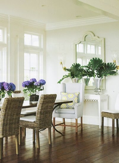 Dining room with wood floor, wicker chairs with an upholstered chair at the head of hte table, and a large, white accent mirror