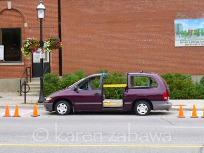 Burgundy van and orange parking cones are part of an art installation outside old Post Office in Port Credit.